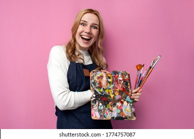 Young happy girl artist with drawing equipment laugh on a pink background, funny student of art school