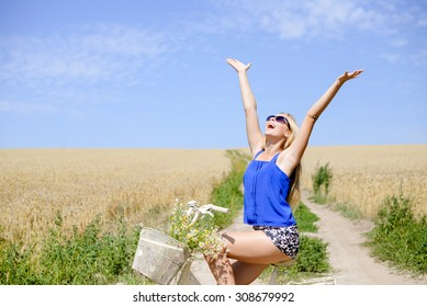 Young happy girl in blue belly shirt and shorts sitting on bicycle lifting her arms with joy riding along earth road in field of wheat, on sunny day outdoors background