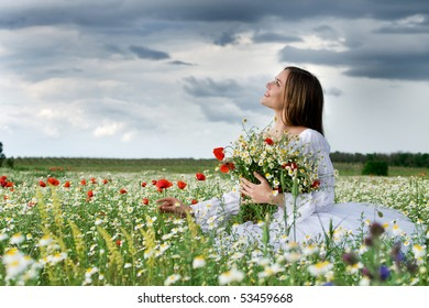 young happy girl with bouquet in daisy field