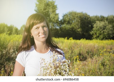 young happy girl with bouquet in daisy field.