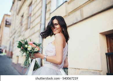 young and happy girl with a bouquet walking down the street