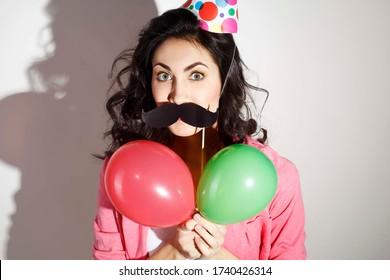 Young happy girl celebrates birthday with a colored cardboard cone hat with balloons and a black cardboard mustache on a stick over white background