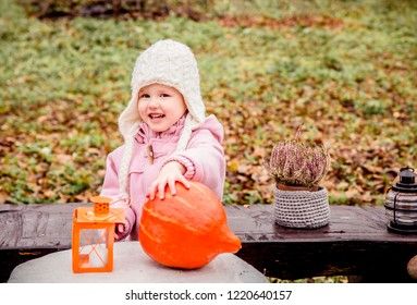 Young happy girl child with wide sly smile posing outdoors with autumn harvest touching pumpkin and wearing warm vintage coat and knitted white hat, autumn leaves and grass on the background.