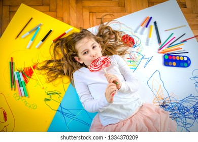 Young happy girl drawing and play with lollipop.