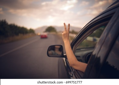 Young happy young girl drives a car a holds her hand out from the window. Lady driver enjoys driving and shows Ok sign with her hand out of window. Road trip, travel and freedom concept.