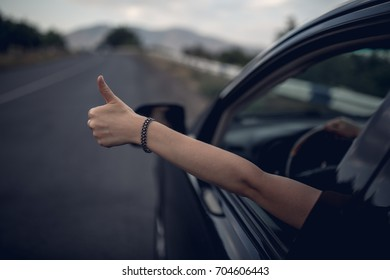 Young happy young girl drives a car a holds her hand out from the window. Lady driver enjoys driving and shows LIKE sign with her hand out of window. Road trip, travel and freedom concept.