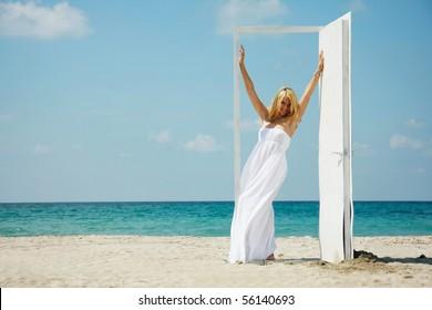 young happy girl entering open door on sea background