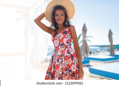 young happy girl with flower dress on tropical sea and beach background, smiling happy girl outdoor portrait,tropical fruits and smoothie, Healthy eating. Beauty, cosmetics.straw and lips,Hat