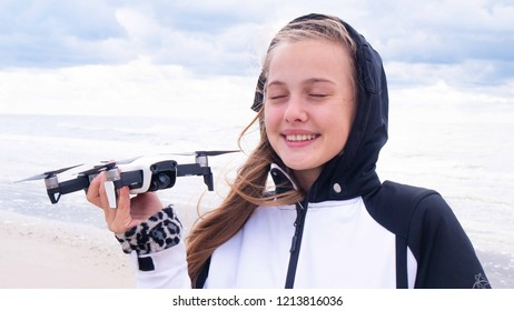 Young happy girl holding white drone on the beach. Windy weather white colors. Laughing girl with her gift quadcopter