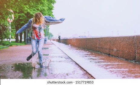 Young happy girl jumping in a puddle on the road under summer rain. Positive funny woman splashing water legs on a rainy day in the city. Feet in shoes or rubber boots. Spring season and rain concept