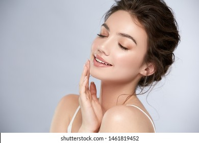 young and happy girl with light make-up and closed eyes touching her chin and smiling, shiny mua with highlighter and pinky lips