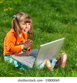 young happy girl on the grass with laptop