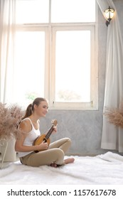 Young happy girl play or practice music on acoustic guitar or ukulele.