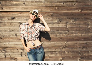 Young happy girl posing against wooden background.