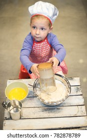 Young happy girl preparing funny cake in the kitchen