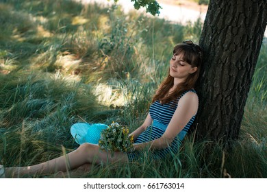 Young happy girl sitting under a tree on a summer