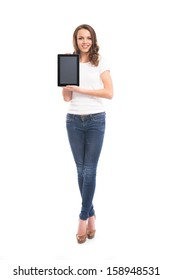 A young and happy girl in stylish jeans holding a tablet computer isolated on a white background.