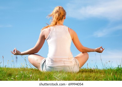 young happy girl training yoga on sunny meadow