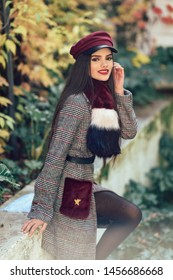 Young happy girl with very long hair smiling and wearing winter coat and cap in autumn leaves background. Lifestyle and fashion concept.