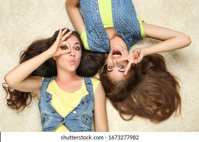 Young happy girlfriends lying on carpet