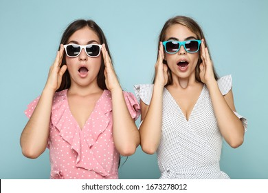 Young happy girlfriends in sunglasses on blue background
