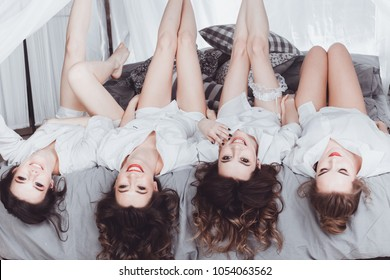 Young happy girls in white shirts are lying on the bed upside down