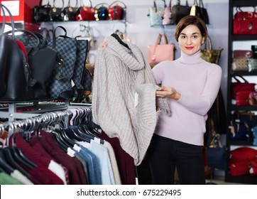 Young happy glad friendly  female shopper examining warm sweaters in womens cloths shop