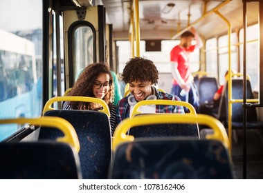 Young happy gorgeous couple is sitting together in a bus and smiling while looking at something hidden behind the bus seat.