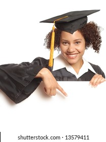 Young, happy, graduating woman pointing at copy space below