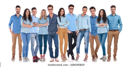 young and happy group of people dressed casual, standing on white background. Two men are wearing glasses and all of them are wearing blue shirts and smiling