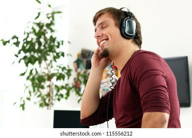 Young and happy guy with headphones listening music at home