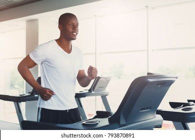 Young happy handsome african-american man in fitness club. Cardio workout, running on treadmill. Healthy lifestyle, guy training in gym. Flare effect, copy space