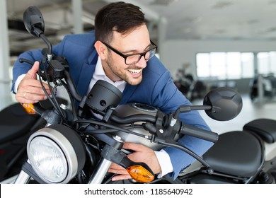 Young happy handsome man choosing a new motorcycle at motorcycle showroom.