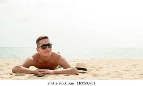 Young happy handsome man lying on stomach taking a sunbath at the beach on summer vacations