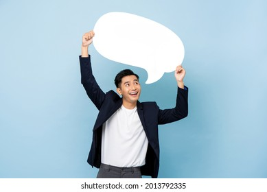 Young happy handsome smiling Asian man holding empty speech bubble in light blue isolated studio background