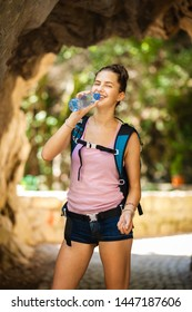 young and happy hiker girl drinking water from a plastic bottle next to a rocky passage