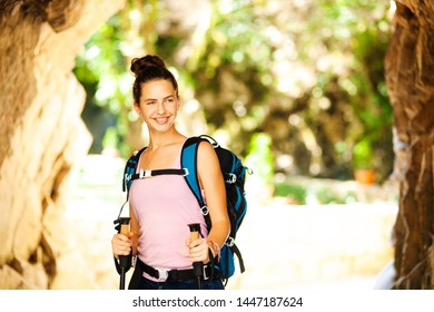 young and happy hiker girl posing next to a rocky passage