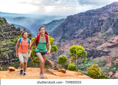 Young happy hikers people walking on Hawaii Waimea Canyon Trail, Kauai island, USA. Asian woman and man couple trekkng in scenic mountain background. Hiking adventure in nature.