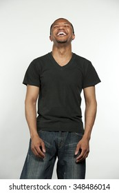 A young happy hip African American male wearing a black t-shirt in a studio setting on a white background.