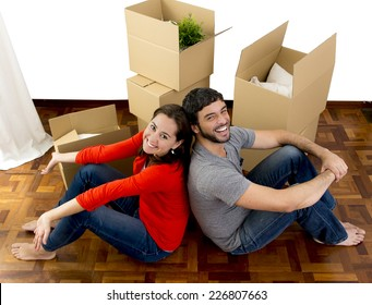 young happy Hispanic couple moving together in a new house , flat or apartment unpacking cardboard boxes home belongings smiling in housing and real state concept