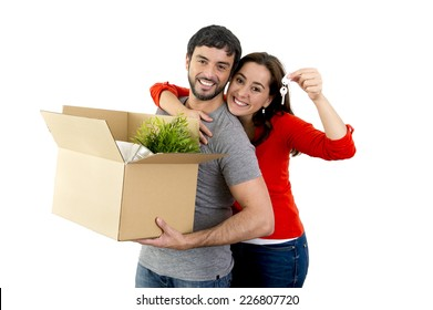 young happy Hispanic couple moving together in a new house , flat or apartment carrying cardboard boxes home belongings smiling in housing and real state concept