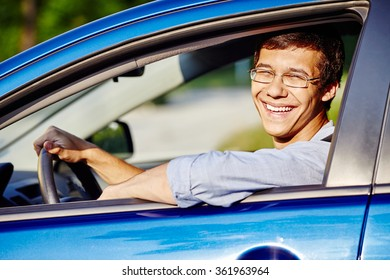 Young happy hispanic man wearing glasses and blue jeans shirt sitting behind wheel of his car and smiling through window - new drivers concept