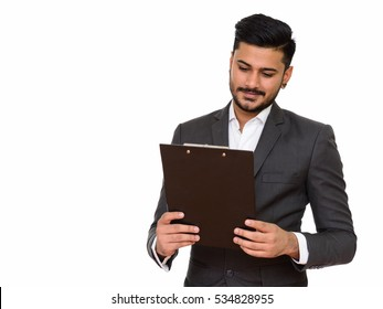 Young happy Indian businessman reading clipboard