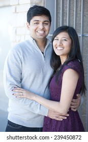 A young and happy Indian couple on a metal steel gray background on a sunny day.