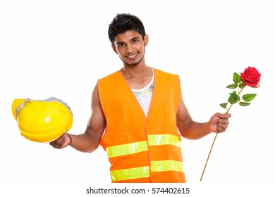 Young happy Indian man construction worker smiling while holding safety helmet and red rose ready for Valentine's day