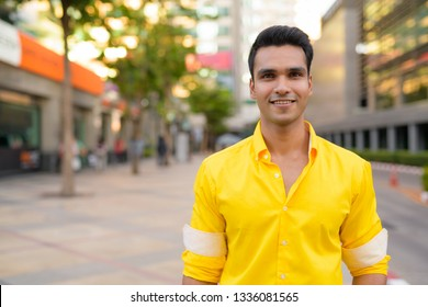 Young happy Indian man smiling in the city streets outdoors
