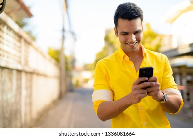Young happy Indian man using phone in the streets outdoors