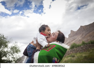 young and happy indian woman lifting up her baby in spiti valley