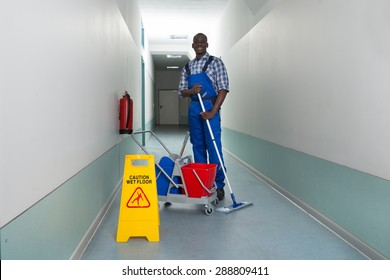 Young Happy Janitor Holding Mop With Bucket And Wet Floor Sign In Corridor