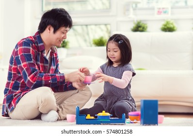 Young  happy japanese father playing with his cute little daughter at home